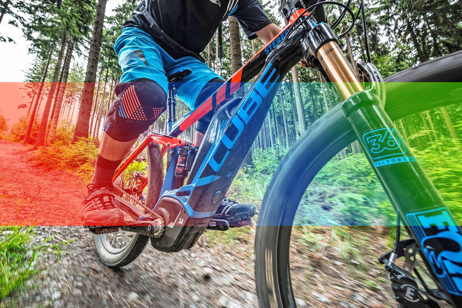 Ein Mountainbiker bei der Abfahrt im Wald, mit einem E-Bike aus dem Cube Store Zella-Mehlis und Werra Bikes Hildburghausen