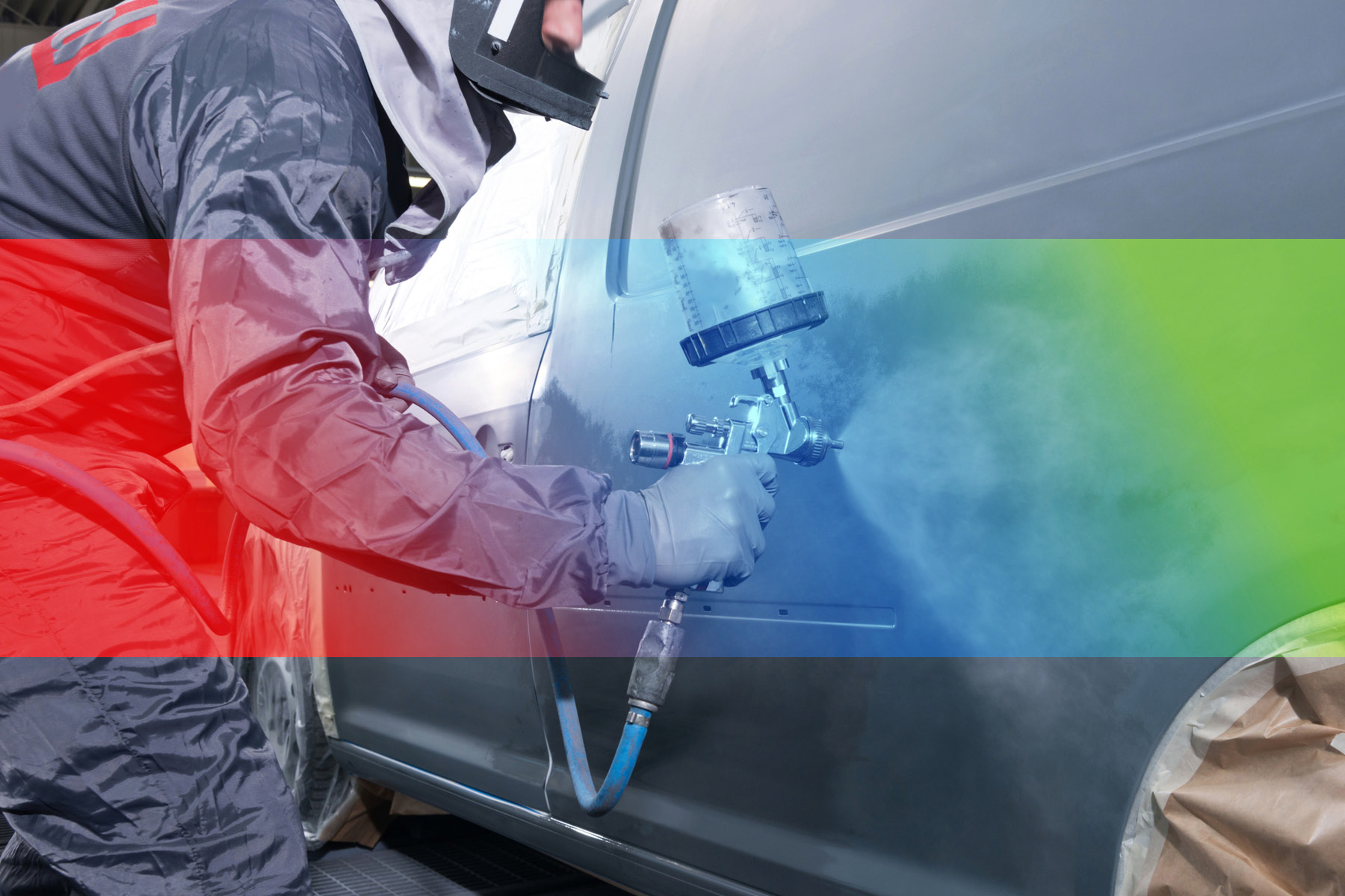 Ein Arbeiter in Schutzkleidung führt die Fahrzeuglackierung im Lack- und Karosserie-Center Hildburghausen durch.
