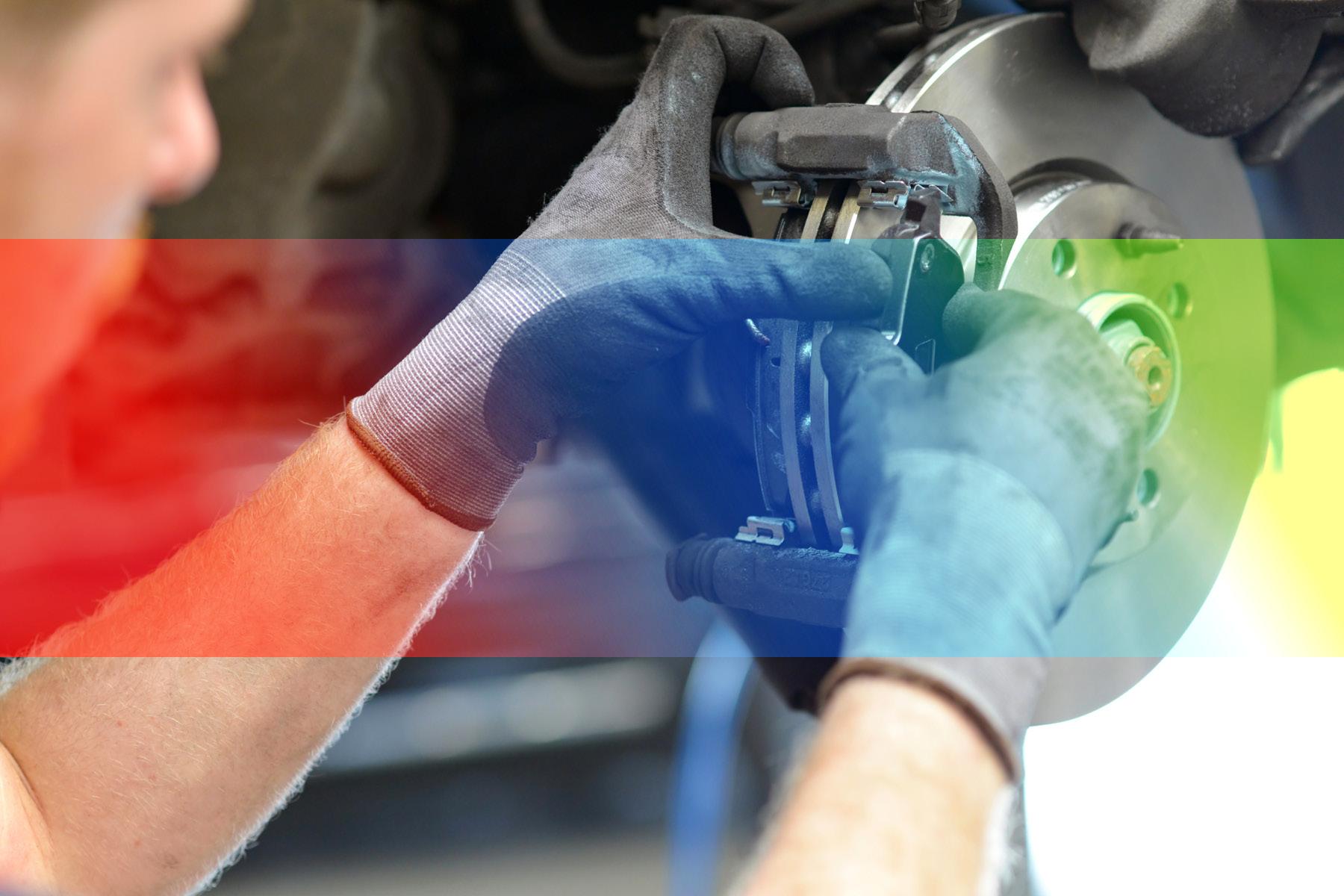Ein Mechaniker mit Schutzhandschuhen repariert eine Bremse im Rahmen des Werkstatt-, Teile- und Reifenservice des Fahrzeughaus Müller